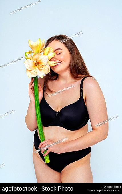 Smiling female model wearing black bikini smelling flowers against white background