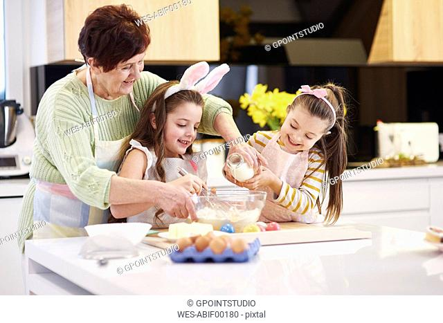 Grandmother and granddaughters baking Easter cookies in kitchen together