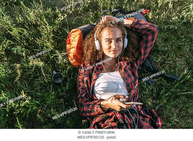 Teenage girl with backpack lying on a meadow listening music with headphones and cell phone