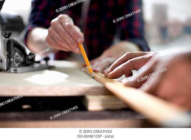 Close up of carpenters marking measurements in furniture making workshop
