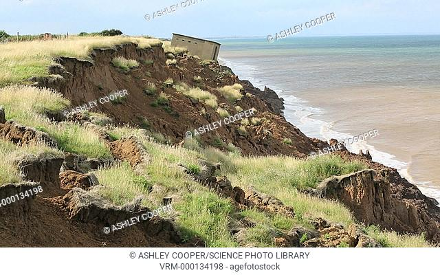 A Second world War lookout post leaning alarmingly and about to tumble over the edge of the cliff near Aldbrough on Yorkshires East Coast, UK