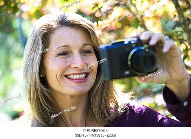 Close-up of a woman holding a camera