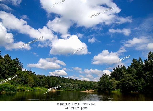 Summer landscape with river, forest and cloudy blue sky. The Gauja is the longest river in Latvia, which is located only in the territory of Latvia