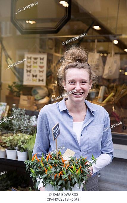 Portrait smiling female florist holding potted plant at storefront