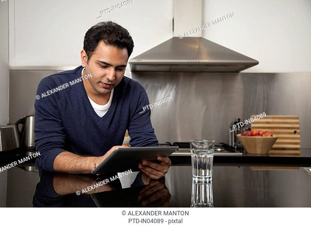 Singapore, Young man relaxing with tablet pc in kitchen