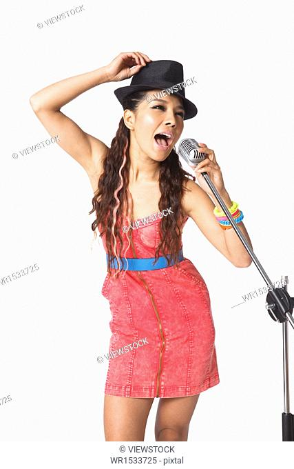 Holding a microphone singing young woman