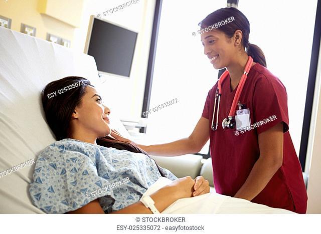 Nurse Talking To Female Patient On Ward