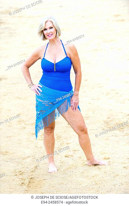 A 56 year old blond woman wearing a swim suit standing on a beach