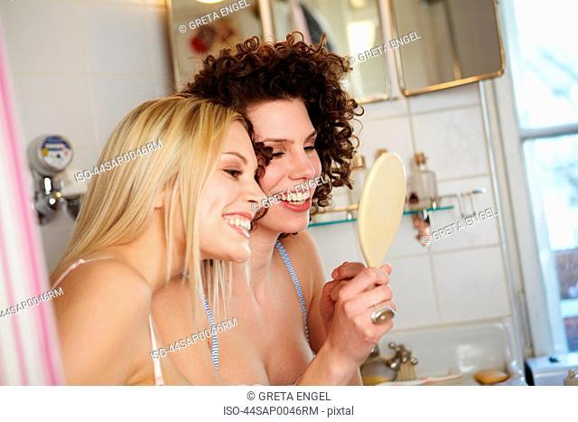 Women checking their teeth in mirror