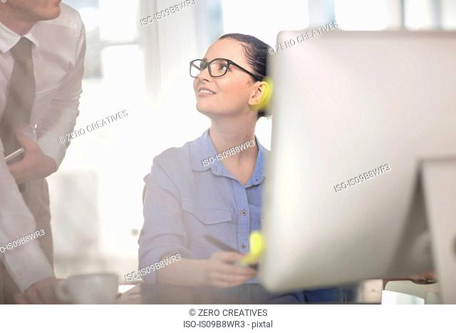 Young female office worker having discussion with colleague at desk