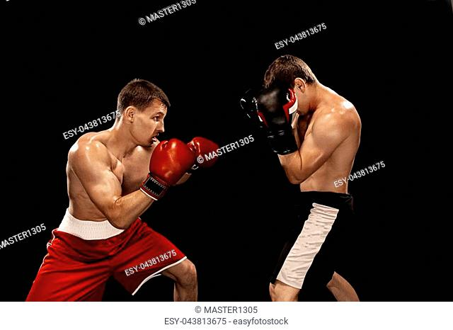 Two professional boxer boxing on black studio background