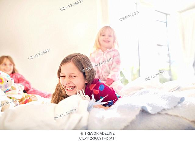 Laughing sisters playing on bed