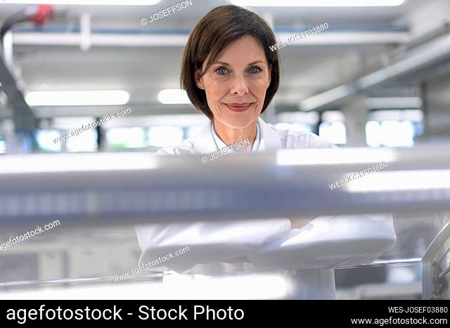 Female scientist by machinery in industry