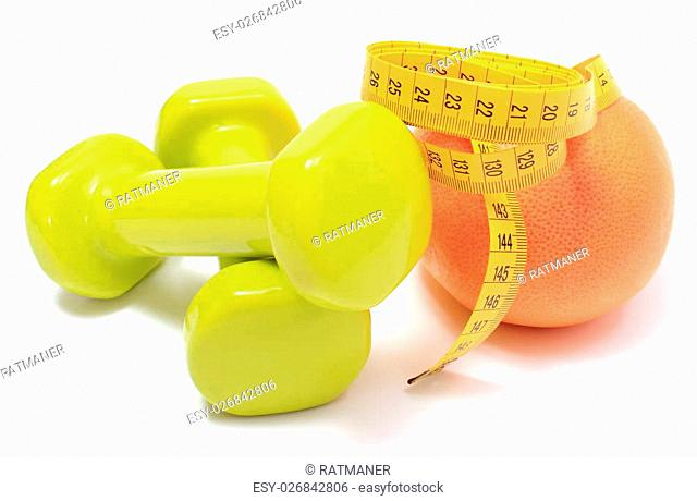 Green dumbbells for using in fitness, fresh grapefruit and tape measure, concept for slimming, healthy nutrition and lifestyle