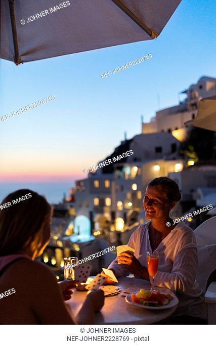 Women playing cards at dusk