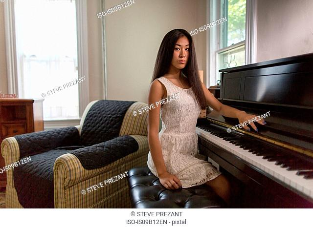 Portrait of sullen teenage girl pianist sitting at piano