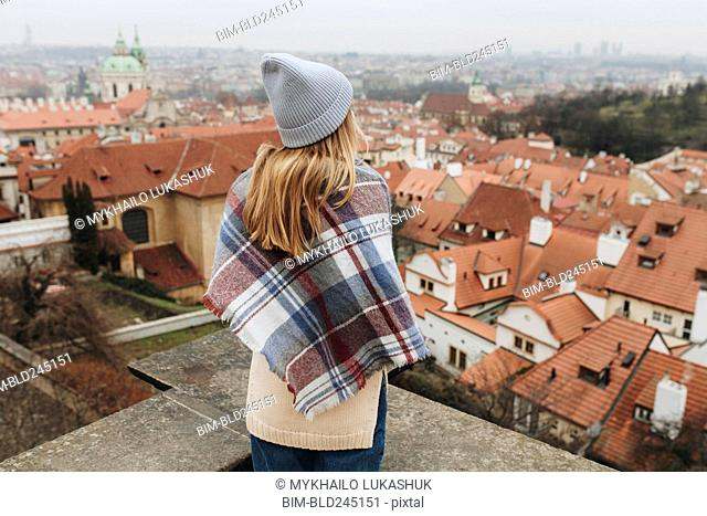 Caucasian woman admiring cityscape from rooftop