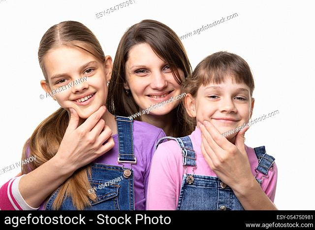 Mom cheerfully holds the children by the chin and looks in the frame