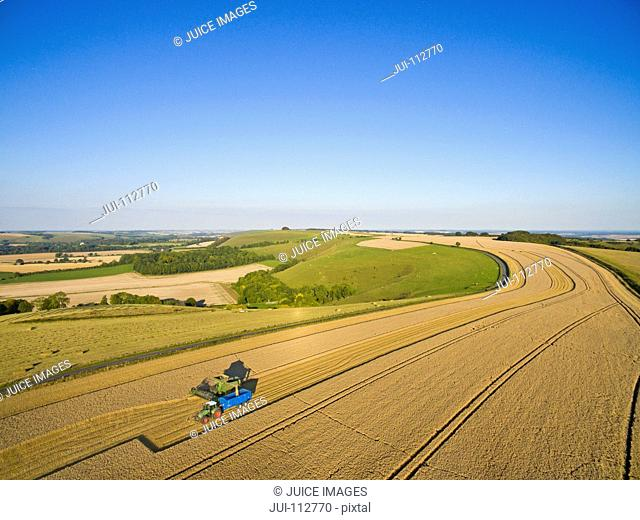 Scenic aerial landscape view of combine harvester filling tractor trailer in sunny barley field under blue sky