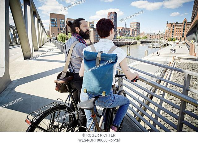 Germany, Hamburg, couple with electric bicycles on a bridge