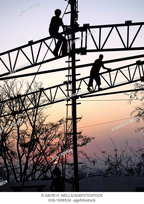 Silhouette of man working on metal frame during sunset, Mysore, India