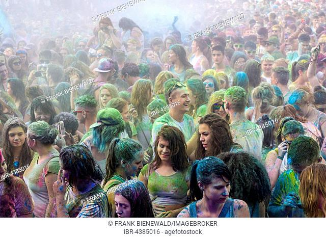 Thousands of young women and man are hardly visible because of color powder in the air at the colorful Holi festival, Dresden, Saxony, Germany