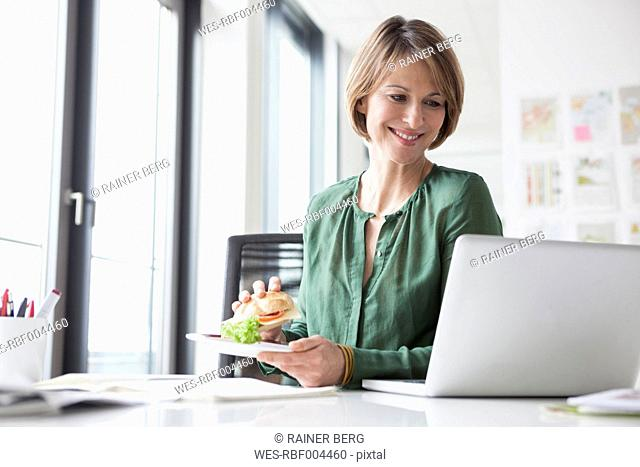Smiling businesswoman having lunch break at office desk