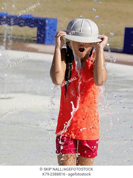 A little girl playing in the water at a water park