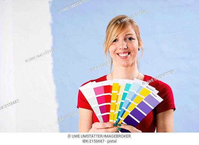 Young woman holding colour cards in front of a wall