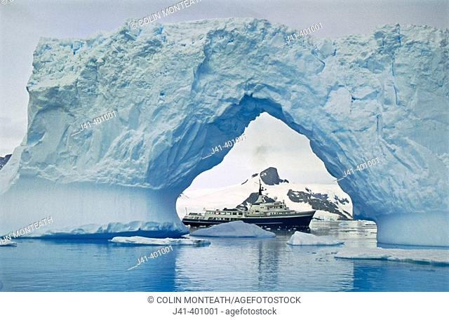 Motor yatch 'Itasca' framed in iceberg arch, Petermann Island, Antarctic peninsula