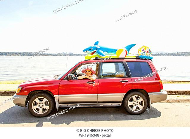 Woman in a car with beach toys and floaties on the roof