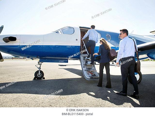 Business people boarding airplane on runway