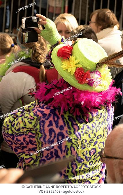 Carnival reveller in green staw hat, magenta boa and leopard skin photographing the Easter Parade in Cassel, France