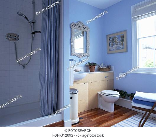 Blue curtain on shower cabinet in blue traditional bathroom