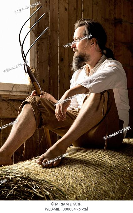 Farmer sitting with hay fork in barn