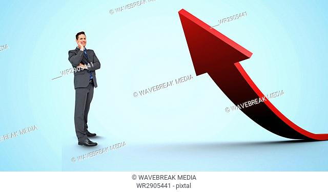 Digital composite image of businessman standing by red arrow
