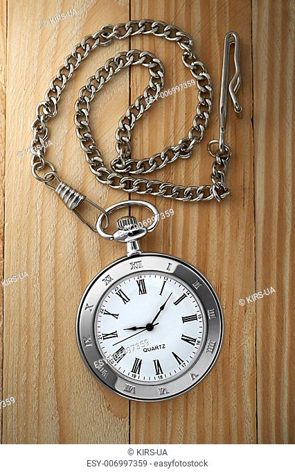 Photo of silver vintage pocket watch with chain on wooden background