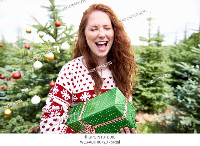 Portrait of redheaded woman with Christmas present crying of joy