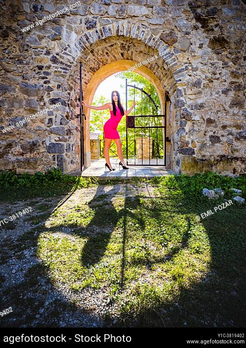 Fanciful young woman looking at camera is framed under arch casting her shadow in foreground