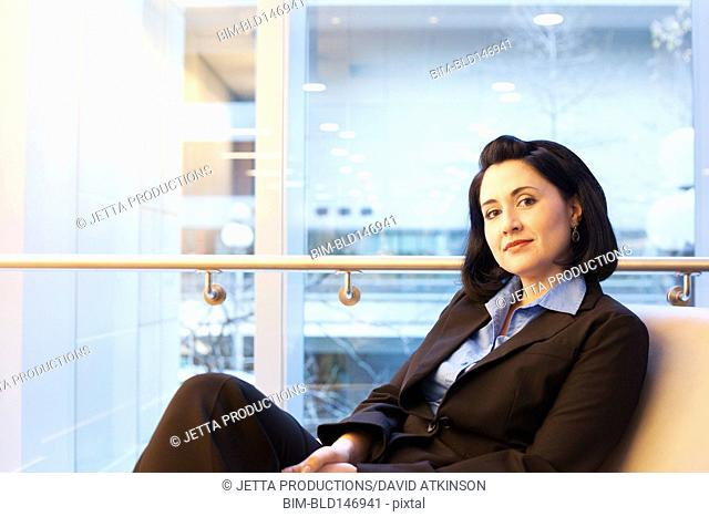 Mixed race businesswoman sitting in office