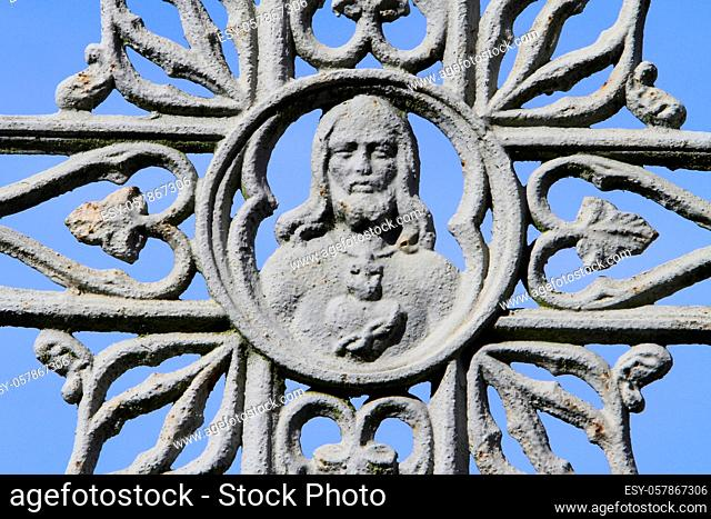 Face of Jesus Christ on a gray metal cross against blue sky. Coulommiers. Seine et Marne. France. Europe