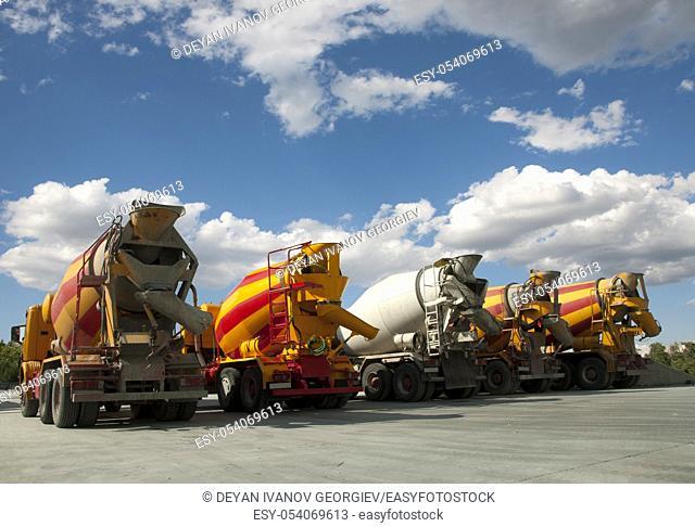 Five Cement Trucks on blue sky