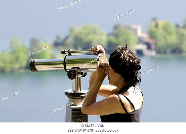 Woman watching with a telescope and islands in background