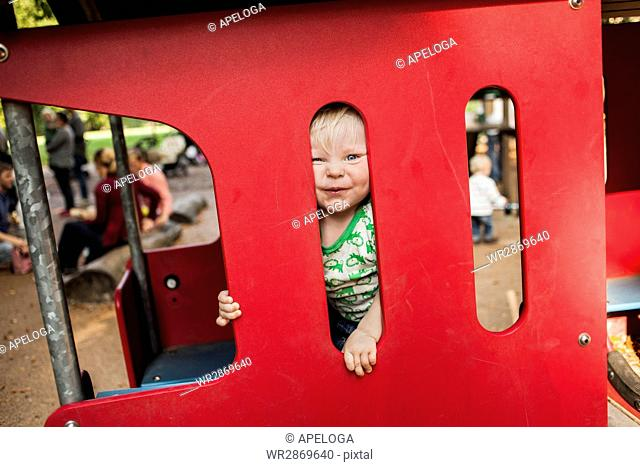 Portrait of baby boy looking through miniature train at park