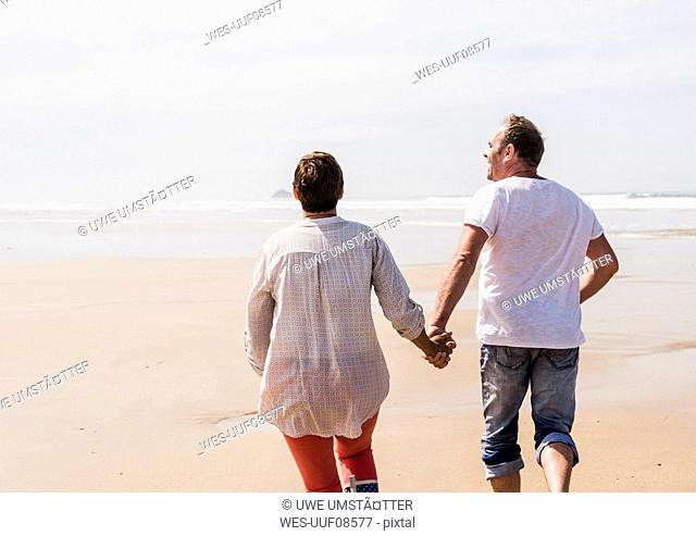 Mature couple running on the beach