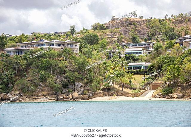 The turquoise Caribbean sea and a tourist resort seen from a boat tour Antigua and Barbuda Leeward Islands West Indies