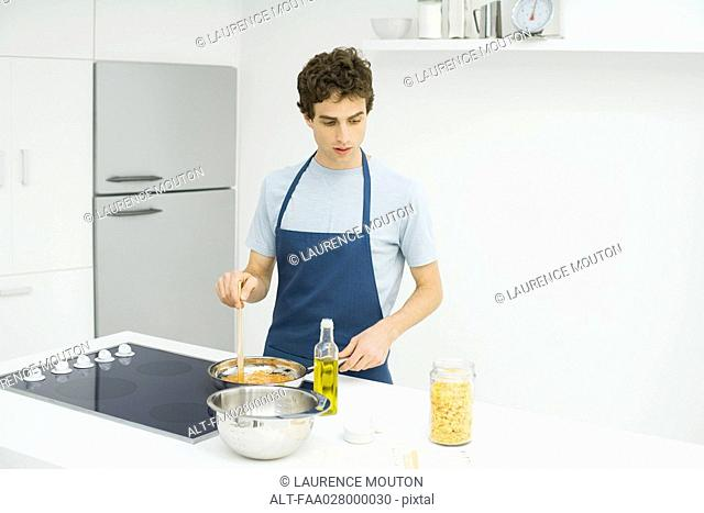 Man standing at stove, cooking, looking down at recipe