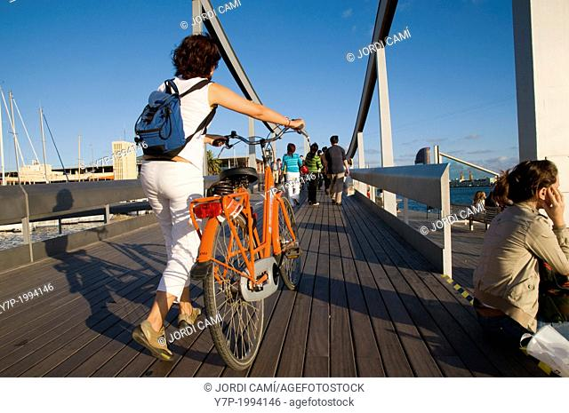 Young woman with a bicycle at Rambla del Mar footbridge to Maremagnum area , Barcelona harbour, Catalonia, Spain