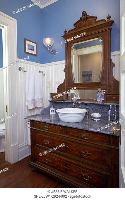 MASTER BATHROOM: View towards large Victorian dresser coverted to bath vanity,grey marble top, bowl sink, white wainscoting 3/4 up wall. blue walls