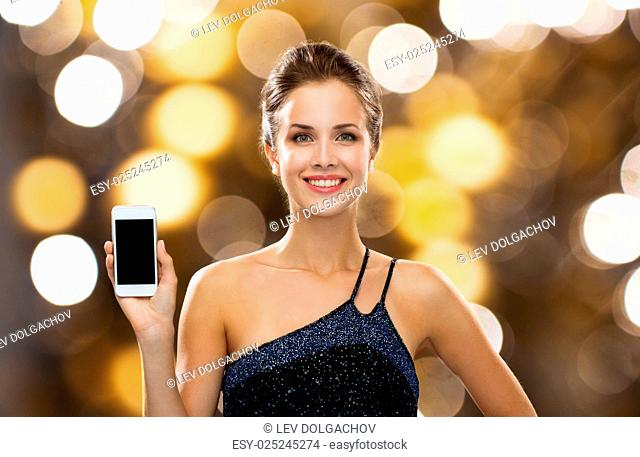 technology, advertisement, holidays and people concept - smiling woman in evening dress with blank smartphone screen over black background